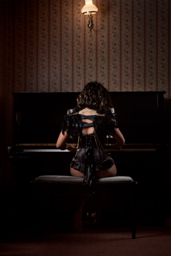 A petite Asian woman sits at an upright piano with her back to the camera, wearing satin lingerie, a corset and feathered pauldrons in all black.