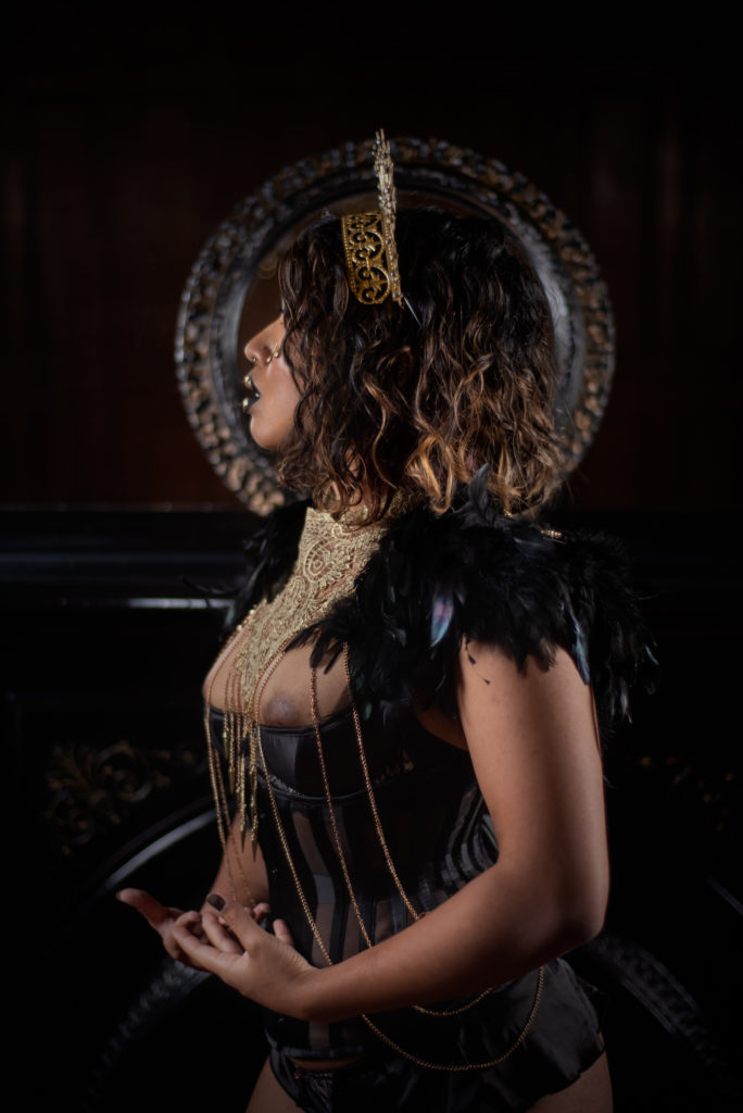 A mysterious woman with gold-tipped curls draped in black feathers and gold chains looks to one side, haloed in filigree gold. Her breasts are barely contained by her satin lingerie.